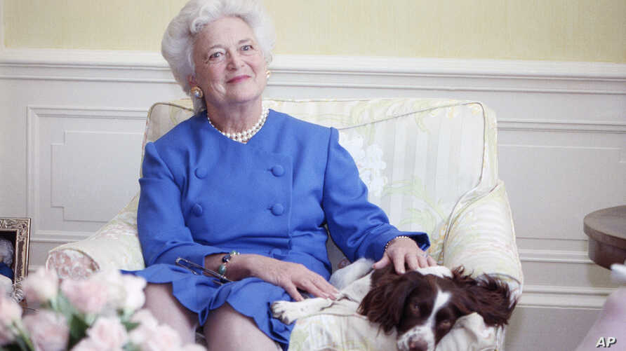 FILE - First Lady Barbara Bush poses with her dog Millie in 1990.
