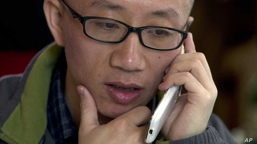 Chinese dissident Hu Jia talks on his phone during a meeting at a restaurant in Beijing, April 10, 2013.