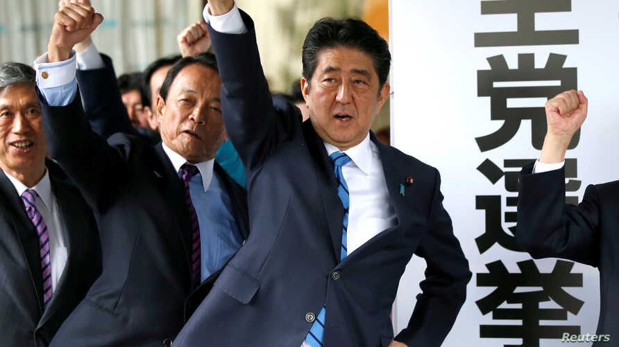 Japan's Prime Minister Shinzo Abe (3rd L) and his party's lawmakers raise their fists as they pledge to win in the upcoming lower house election, at their party headquarters in Tokyo, Japan September 28, 2017.