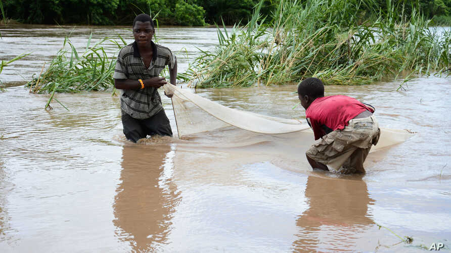 Children work to salvage goods washed away by floodwaters in the southern district of Chikwawa, near Blantyre, Malawi, Jan, 15, 2015.
