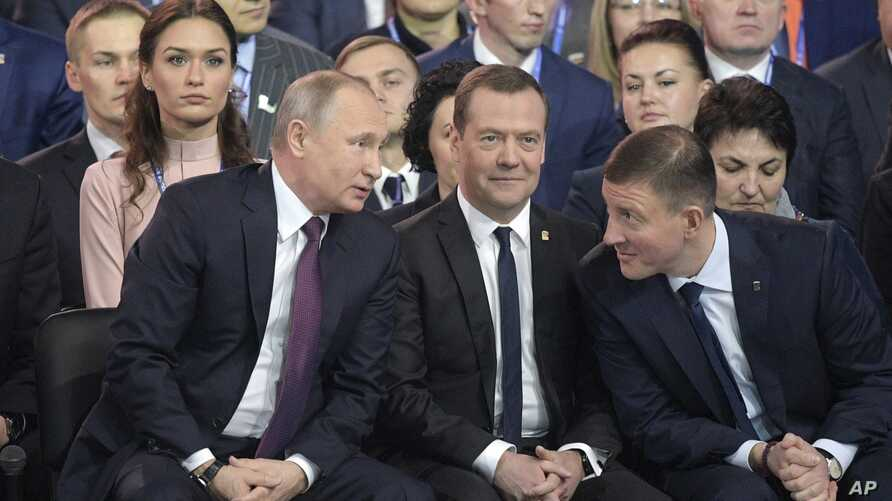 Russia ElectionRussian President Vladimir Putin, foreground left, speaks to Russian Prime Minister Dmitry Medvedev, center, and acting Secretary of the General Council of United Russia Andrey Turchak , right, at the United Russia party congress in Mo