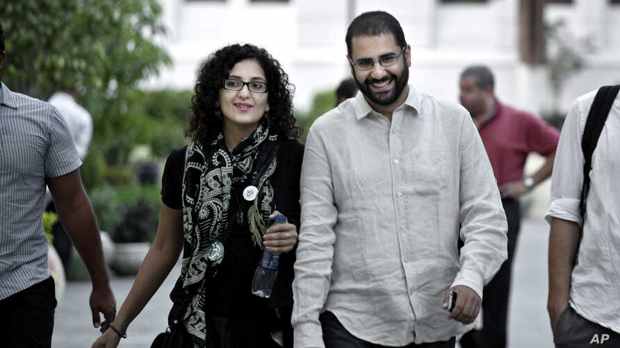 FILE - One of Egypt's most prominent activists, Alaa Abdel-Fattah, walks with his sister Mona Seif before a conference at the American University in Cairo, near Tahrir Square, Egypt, Sept. 22, 2014.