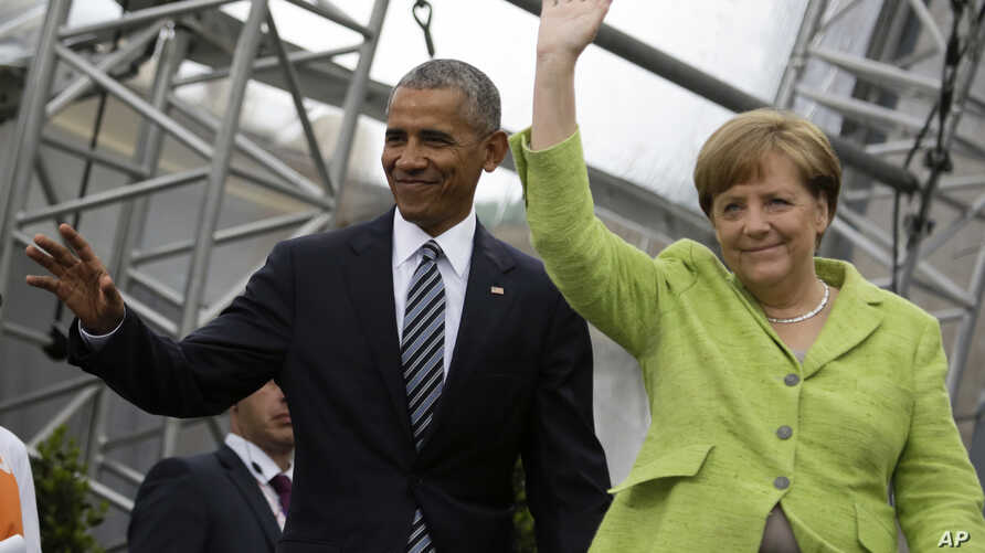 Former U.S. President Barack Obama, left, and German Chancellor Angela Merkel, right, arrive for a discussion event on democracy and global responsibility at a Protestant conference in Berlin, Germany, May 25, 2017.