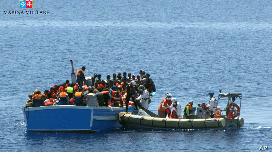 Members of an Italian Navy unit, in the boat at right, rescue migrants in the Mediterranean Sea, May 3, 2015.