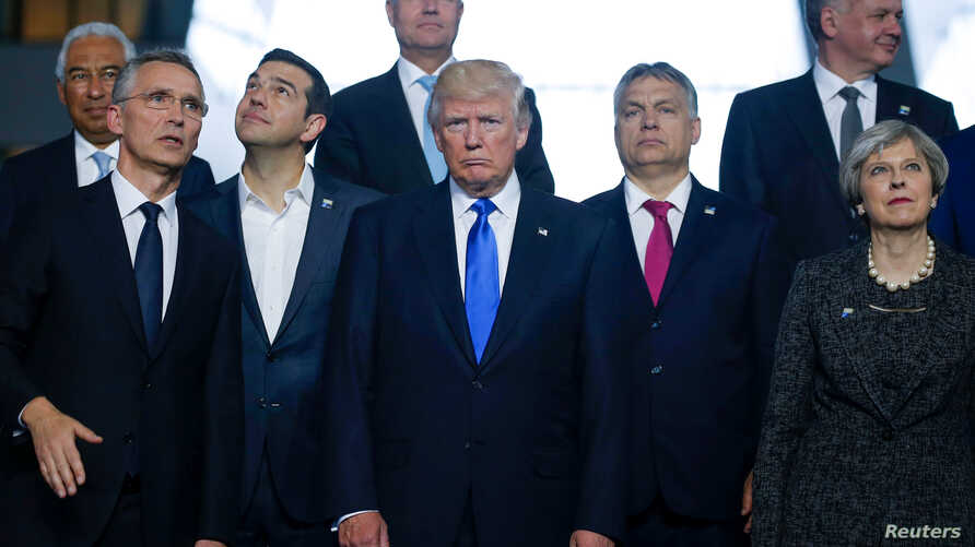 From left, NATO Secretary General Jens Stoltenberg, Greek Prime Minister Alexis Tsipras, U.S. President Donald Trump, Hungarian Prime Minister Voktor Orban and Britain's Prime Minister Theresa May pose for a family photo during a NATO summit at their