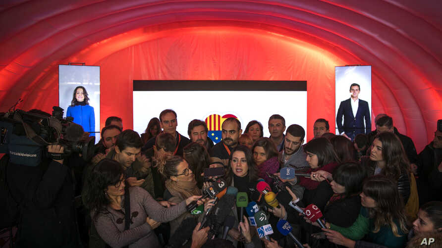 Ines Arrimadas, center, leader of the Citizens Party and candidate for the upcoming Catalan regional election, speaks with journalists during a campaigning event in Barcelona, Dec. 19, 2017.