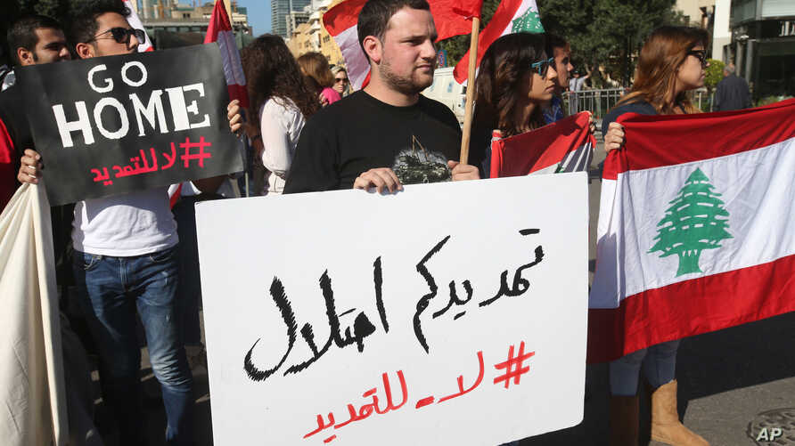 "Activists hold Lebanese flags and an Arabic placard, center, that reads: ""your extension is an occupation, no to the extension,"" during a protest against the extension of the Lebanese parliament, on a road that leads to the Parliament building, in do"