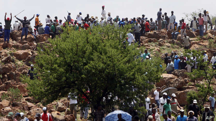 FILE - Miners gather on a hill during their strike at the AngloGold Ashanti Mine in Fochville near Johannesburg, South Africa, Oct. 19, 2012.