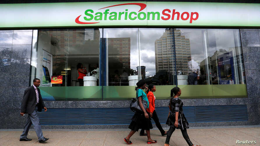 Pedestrians walk past a mobile phone care centre operated by Kenyan's telecom operator Safaricom in the central business district of Kenya's capital Nairobi, May 11, 2016.