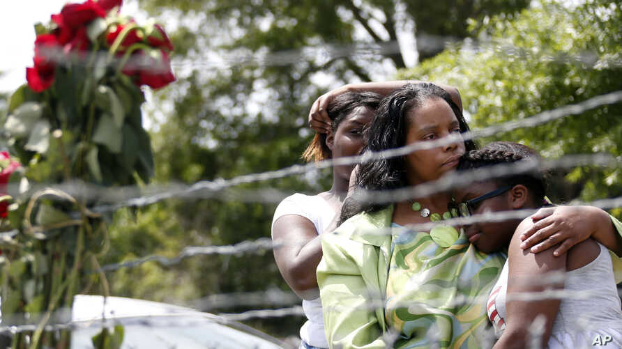 Area residents, from left, Waynetta Theodore, Alberta Harris and Christiena Preston console each other as they pay their respects at a makeshift memorial near the site where two Mississippi police officers were killed in Hattiesburg, Miss., May 10, 2