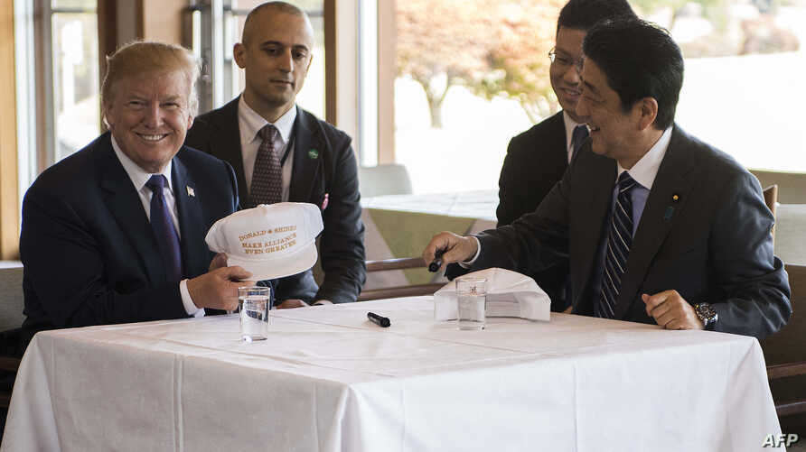 """US President Donald Trump speaks with Japan's Prime Minister Shinzo Abe during a luncheon at the Kasumigaseki Country Club Gold Course in Tokyo, Nov. 5, 2017. The president and prime minister signed white hats reading """"Donald and Shinzo Make Allian..."""