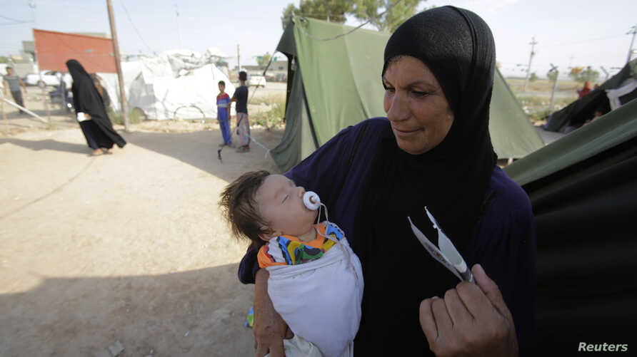 A woman who fled violence in the Iraqi town of Jalawla carries a baby at Ali Awa refugee camp, near Khanaqin city, August 28, 2014. REUTERS/Youssef Boudlal (IRAQ - Tags: POLITICS CONFLICT) - RTR445H5