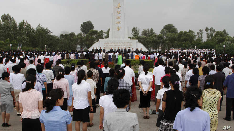 FILE - North Koreans stand together during a meeting in Pyongyang on June 15, 2012, to mark the 12th anniversary of the North-South Joint Declaration.