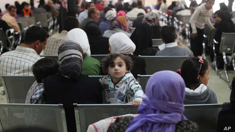 FILE - Syrian refugee families wait to be registered with the UNHCR services, during the Australian Foreign Minister Julie Bishop's visit to the compound, to meet with the  UNHCR representative to Jordan, Andrew Harper, regarding the Syrian refugee s