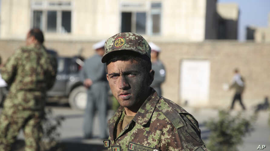 An Afghan National Army soldier who survived a road side bomb explosion, walks by the site of the blast in Kabul, Afghanistan, Oct. 21, 2014.