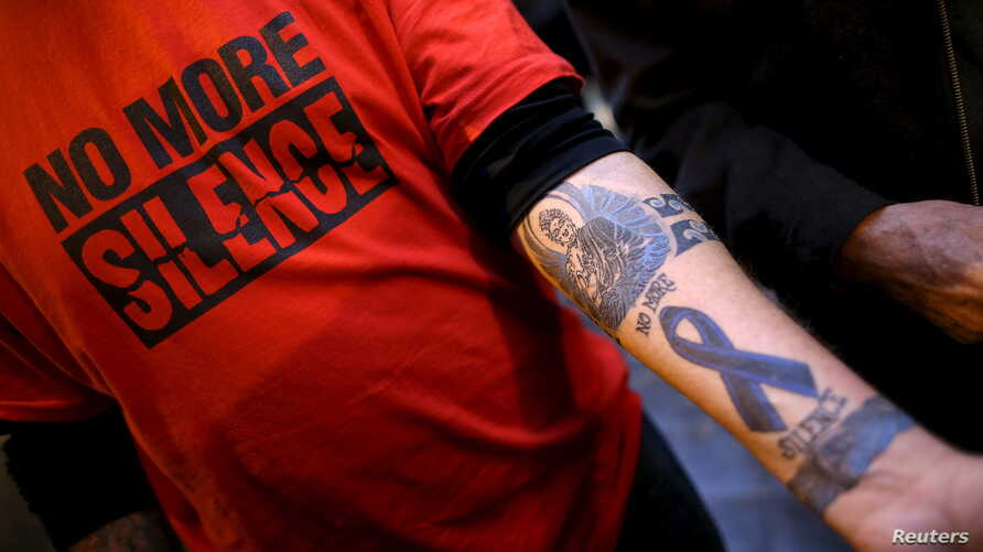 """FILE - Paul Levely, a child sex abuse victim, wears a T-shirt that says """"no more silence"""" and shows a tattoo on his arm in Rome, Italy, Feb. 28, 2016. The Catholic Church in Australia is rejecting laws forcing priests to report confessions of child a..."""