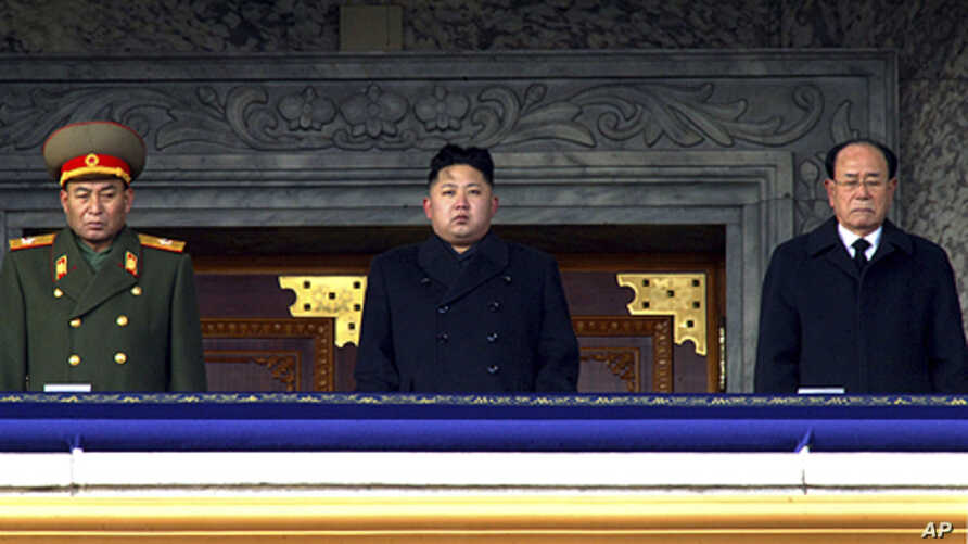 In this photo taken Thursday, Dec. 29, 2011, new North Korean leader Kim Jong Un, center, presides over a national memorial service for his late father Kim Jong Il at Kim Il Sung Square in Pyongyang, North Korea. Flanking him are Kim Yong Nam, presid