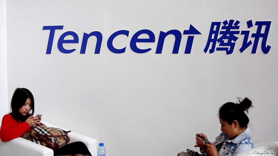 FILE - Visitors use their smartphones underneath the logo of Tencent at the Global Mobile Internet Conference in Beijing, May 6, 2014.