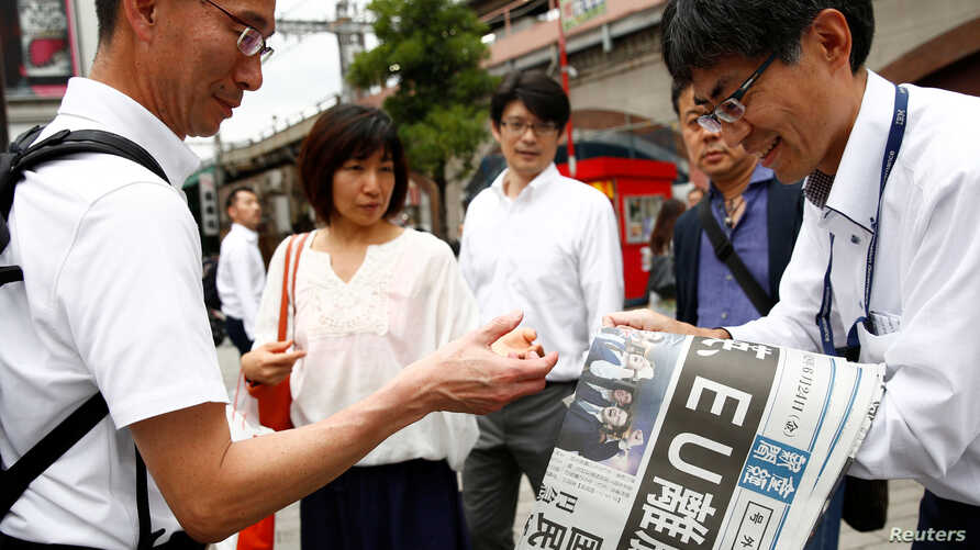 FILE - A man hands out special editions of the Sankei Shimbun newspaper outside a train station in Tokyo, Japan, June 24, 2016.