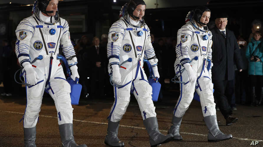 From left: NASA astronaut Jeff Williams, Russian cosmonauts Alexei Ovchinin, and Oleg Skripochka of Roscosmos, members of the main crew of the expedition to the International Space Station (ISS), walk to report to members of the State Committee prior