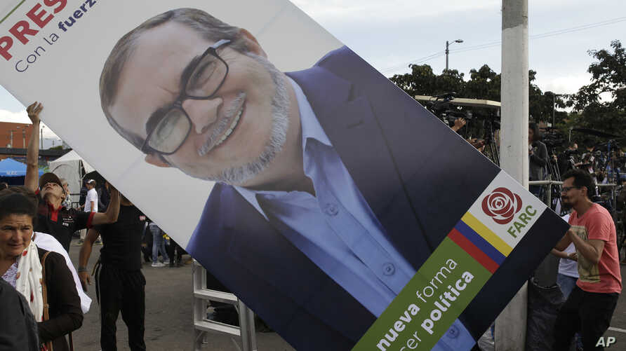 Supporters set up a placard of Rodrigo Londono, known as Timochenko, the presidential candidate of the political party launched by former rebels of the Revolutionary Armed Forces of Colombia, FARC, during an event to present the party's candidates to