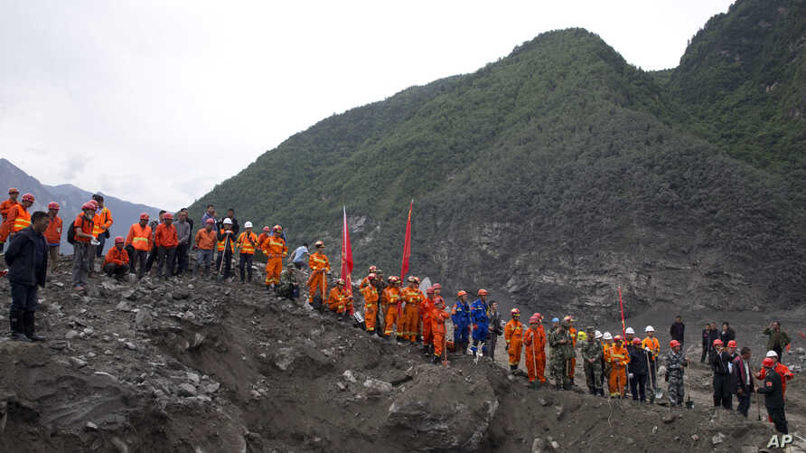 Rescue workers line up along a giant pit as they prepare to search for victims at the site of a landslide in Maoxian County in southwestern China's Sichuan Province, June 25, 2017.