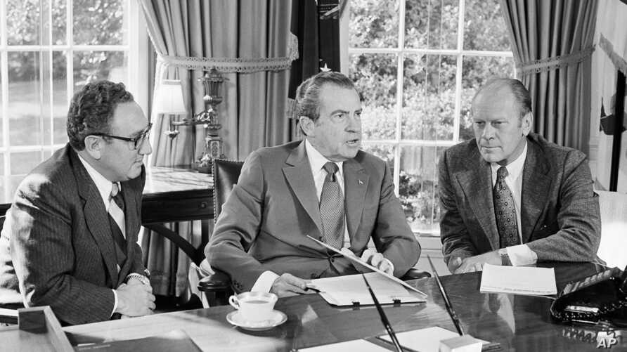 FILE - Then-vice presidential nominee Gerald R. Ford (R) listens as President Richard Nixon, accompanied by Secretary of State Henry Kissinger, speaks in the Oval Office of the White House in Washington, Oct. 13, 1973.