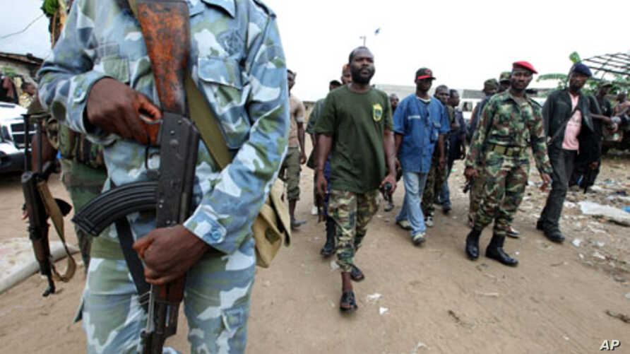 "A man known as Commander Bauer, the chief of a group of fighters which calls itself the ""invisible commandos"", walks with his men in northern Abidjan's Abobo district. Fighting in Ivory Coast's main city is spreading and the death toll from a power s"