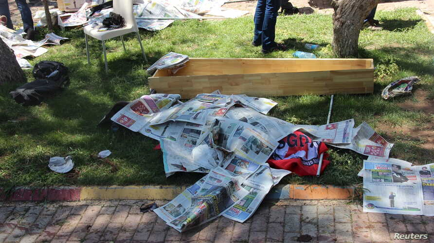 The body of a victim, covered by newspapers, lies next to a coffin after an explosion in Suruc in the southeastern Sanliurfa province, Turkey, July 20, 2015.