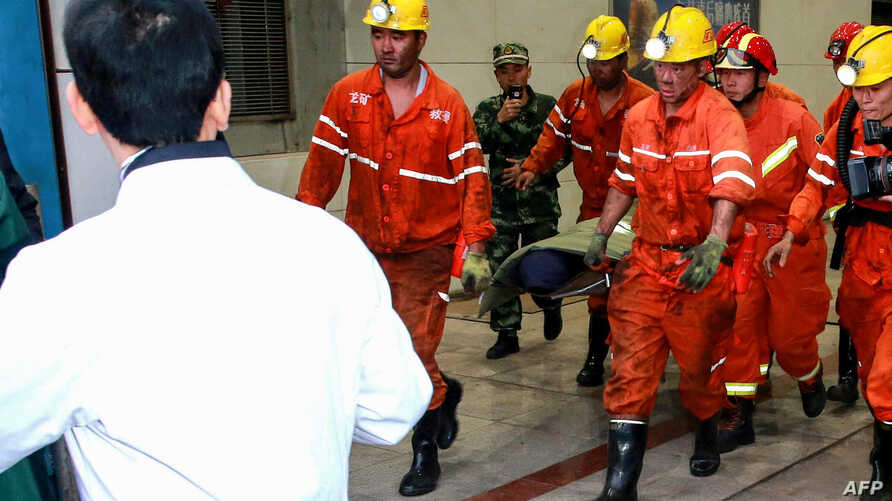 This photo taken on October 21, 2018 shows rescuers transferring an injured miner after a mining accident in Yuncheng County in China's eastern Shandong province. - Nineteen miners have been confirmed dead in east China following a mining accident ea