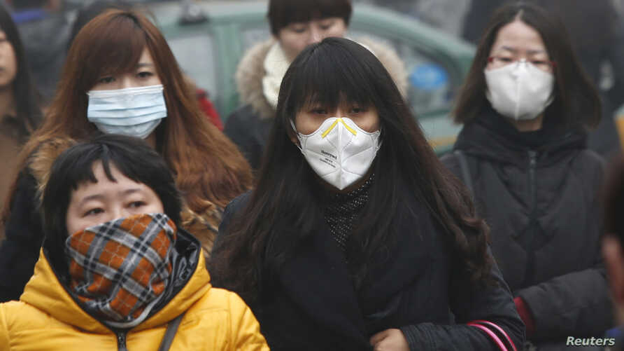Commuters wearing masks make their way amid thick haze in the morning in Beijing February 26, 2014. China's north is suffering a pollution crisis, with the capital Beijing itself shrouded in acrid smog. Authorities have introduced anti-pollution poli...