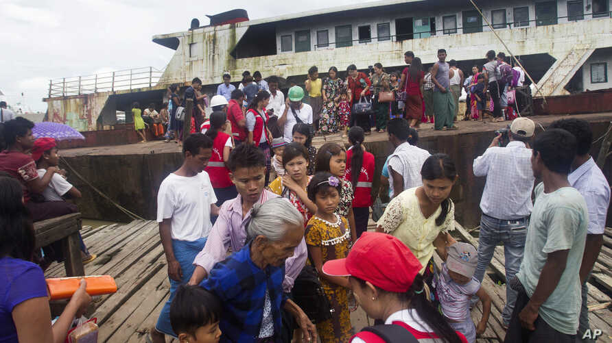 Fleeing Buddhist Rakhine residents arrive by ship from the unrest in Maungdaw region at the jetty, Aug. 29, 2017, in Sittwe, Rakhine State, western Myanmar.