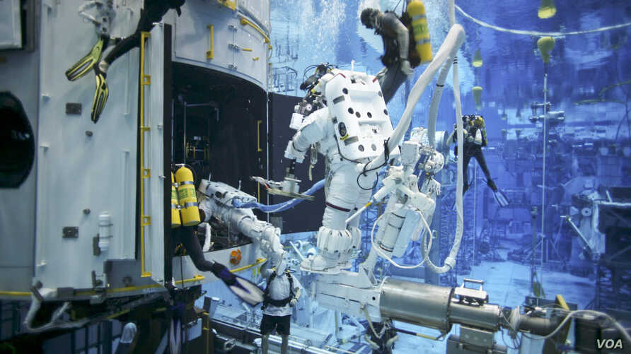Astronauts practice on a Hubble model underwater at the Neutral Buoyancy Lab in Houston under the watchful eyes of NASA engineers and safety divers.