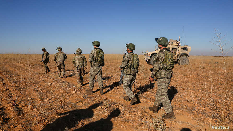 FILE - U.S. and Turkish soldiers conduct the first-ever combined joint patrol outside Manbij, Syria, Nov. 1, 2018, in this U.S. Army handout photo provided by Reuters.