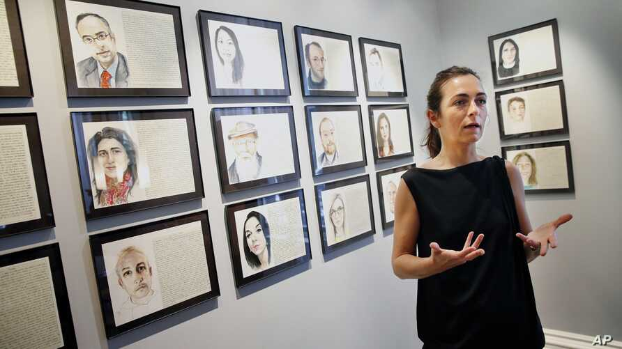 Aurelie Galois speaks with a reporter about her artwork at the French Cultural Center in Boston, June 7, 2016. Every Friday for a year, French artist Galois painted a portrait of a stranger as a way to get acquainted with her adoptive city of Boston.