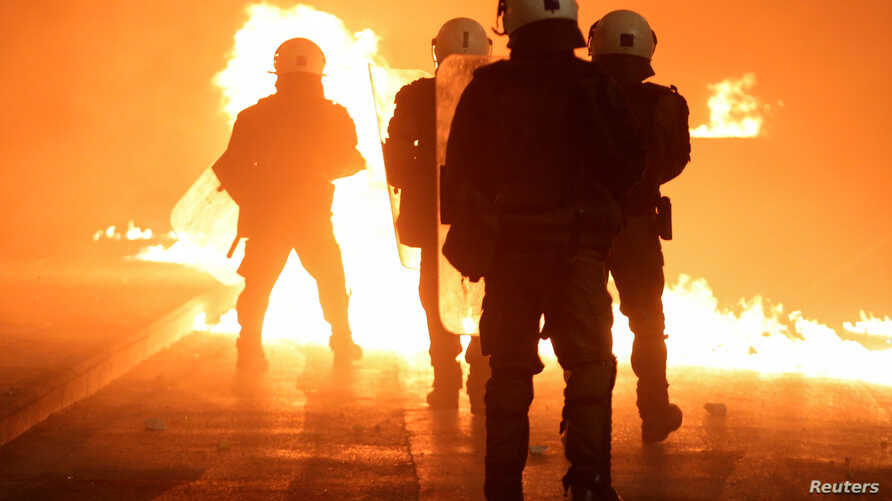 A petrol bomb explodes next to riot police as clashes erupted during an anniversary rally marking the 2008 police shooting of 15-year-old student Alexandros Grigoropoulos, in Thessaloniki, Greece, Dec. 6, 2018.