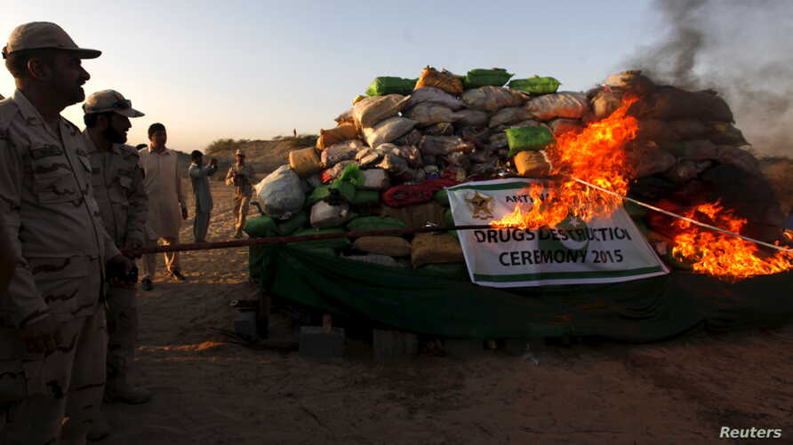 A soldier torches a pile of narcotics during a joint destruction ceremony by the Anti Narcotics Force (ANF) and Pakistan Coast Guards (PCG) on the outskirts of Karachi, Pakistan, Oct. 15, 2015.