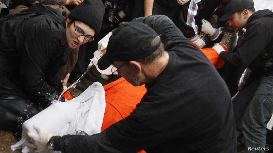 Protestors perform a simulation of the waterboarding torture technique on a man dressed as a prisoner during a protest, marking the fifth anniversary of the U.S.-led invasion of Iraq, in front of the White House in Washington, March 19, 2008.