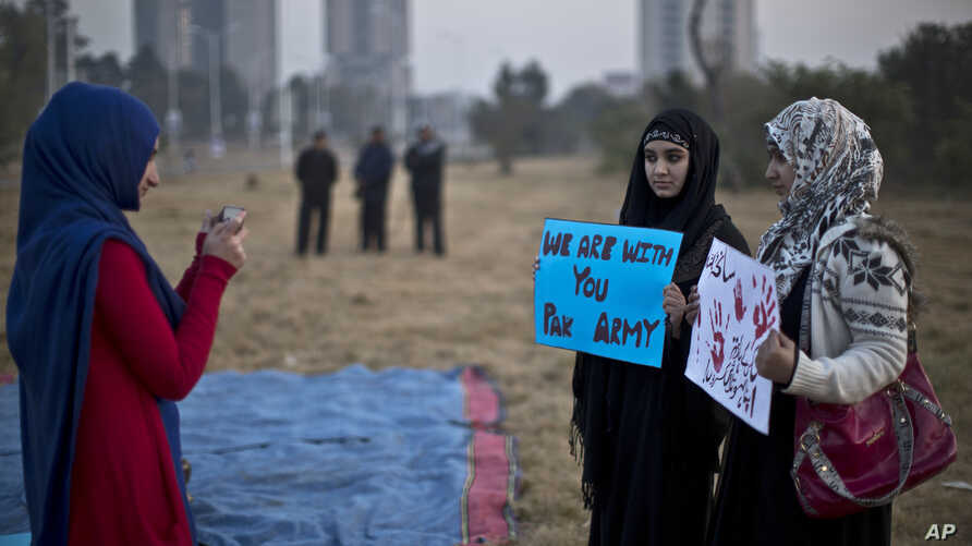 A Pakistani student uses her mobile phone to take a picture of her friends holding banners prior to a protest in Islamabad, Pakistan, Dec. 19, 2014.