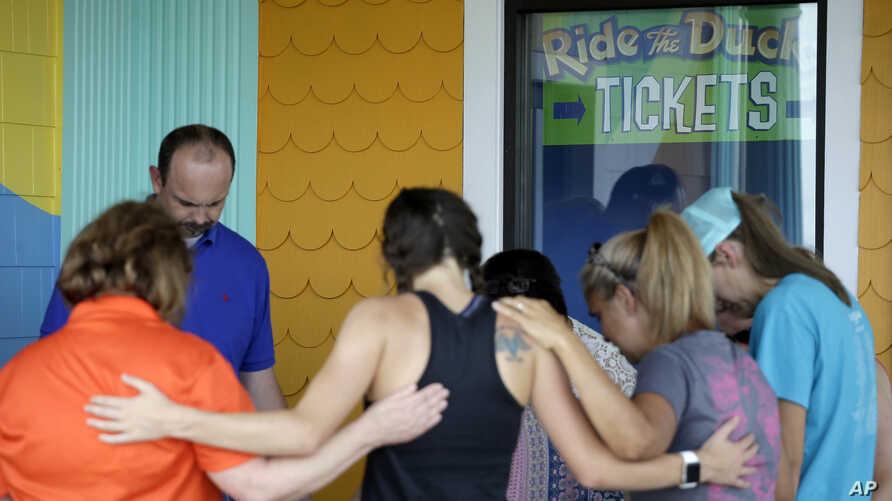 People pray outside Ride the Ducks, an amphibious tour operator involved in an accident on Table Rock Lake, July 20, 2018 in Branson, Missouri.