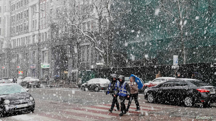 Young people cross a street amid a snow flurry in central Kyiv, Ukraine March 27, 2019. The country holds presidential elections Sunday.