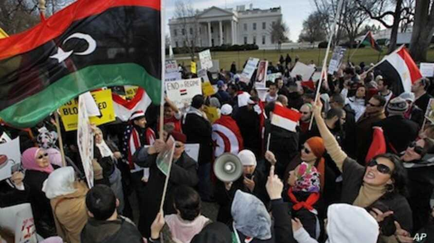 Protesters waving the 1951 first national flag of modern Libya gather in front of the White House in Washington, Saturday, Feb. 26, 2011 condemning Libyan leader Moammar Gadhafi and calling for his ouster.