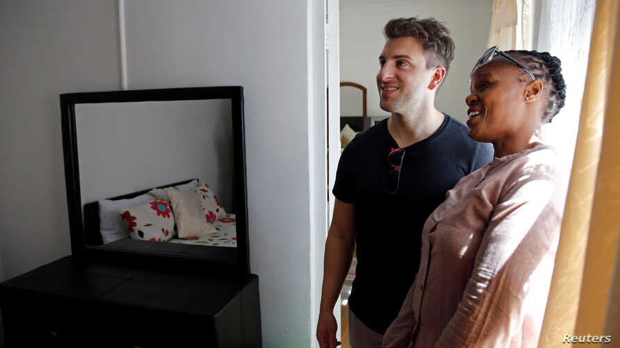 Co-founder and CEO of Airbnb Brian Chesky talks to Linda Pona at her bed and breakfast in Langa township, Cape Town, South Africa, March 17, 2017.
