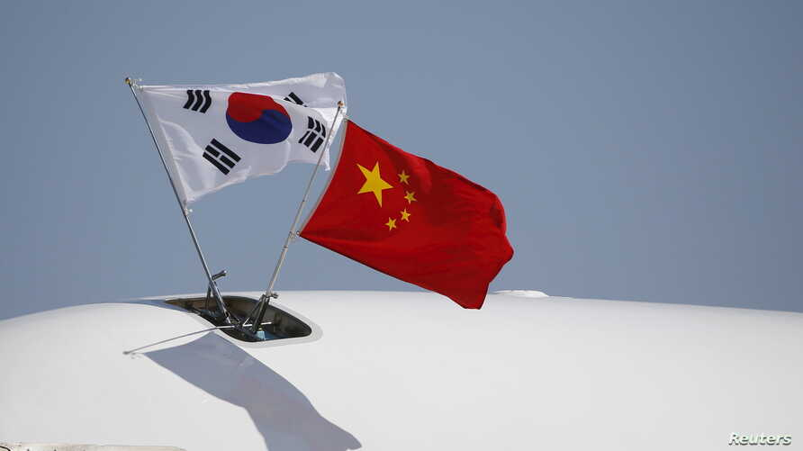 FILE - Flags from South Korea, left, and China flutter atop an aircraft at Beijing Capital International Airport in China, Sept. 2, 2015.