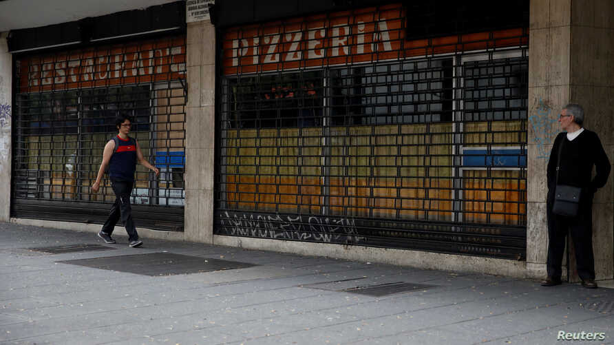 A man walks past closed restaurant during a blackout in Caracas, Venezuela, March 26, 2019.
