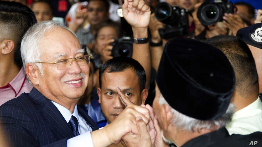 Former Prime Minister Najib Razak, left, shakes hands with his supporters as he leaves Kuala Lumpur High Court after a court hearing in Kuala Lumpur, Malaysia, Sept. 20, 2018.
