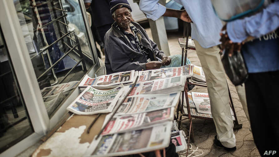 A Street vendor sells newpapers with elections headlines at a central street, Oct. 16, 2014 in Maputo.
