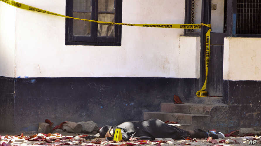 One of the bodies of three women who were shot dead by police lies outside the central police station in the coastal city of Mombasa, Kenya Sunday, Sept. 11, 2016. The three women were killed by police after they attacked the police station using pet