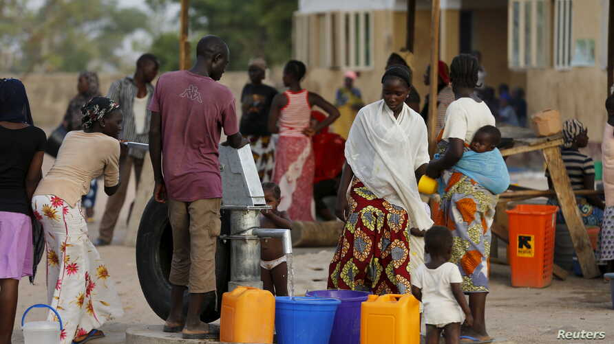 FILE - People gather at a tap in the Malkohi camp for internally displaced people as they collect water in Yola, Nigeria.
