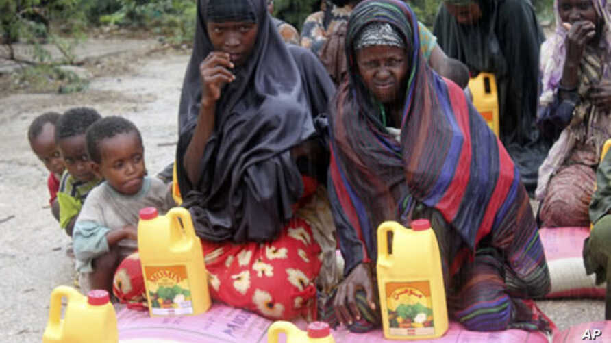 Somali women and children from southern Somalia wait in the rain with some basic rations at a displaced camp in Mogadishu, Somalia, July 15, 2011